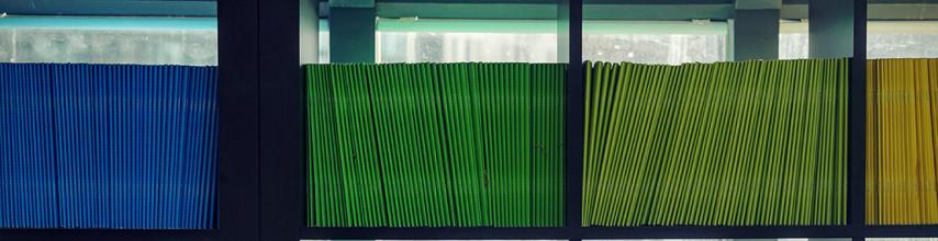 Image of blue, green and yellow folio books on a black bookshelf.